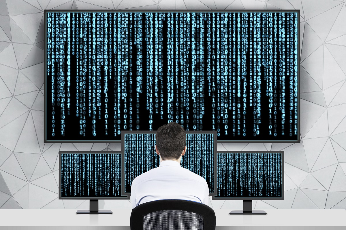 Man seated before multiple computer screens of varying size, all displaying a huge amount of hard to decipher information, is the style used in the Matrix films.