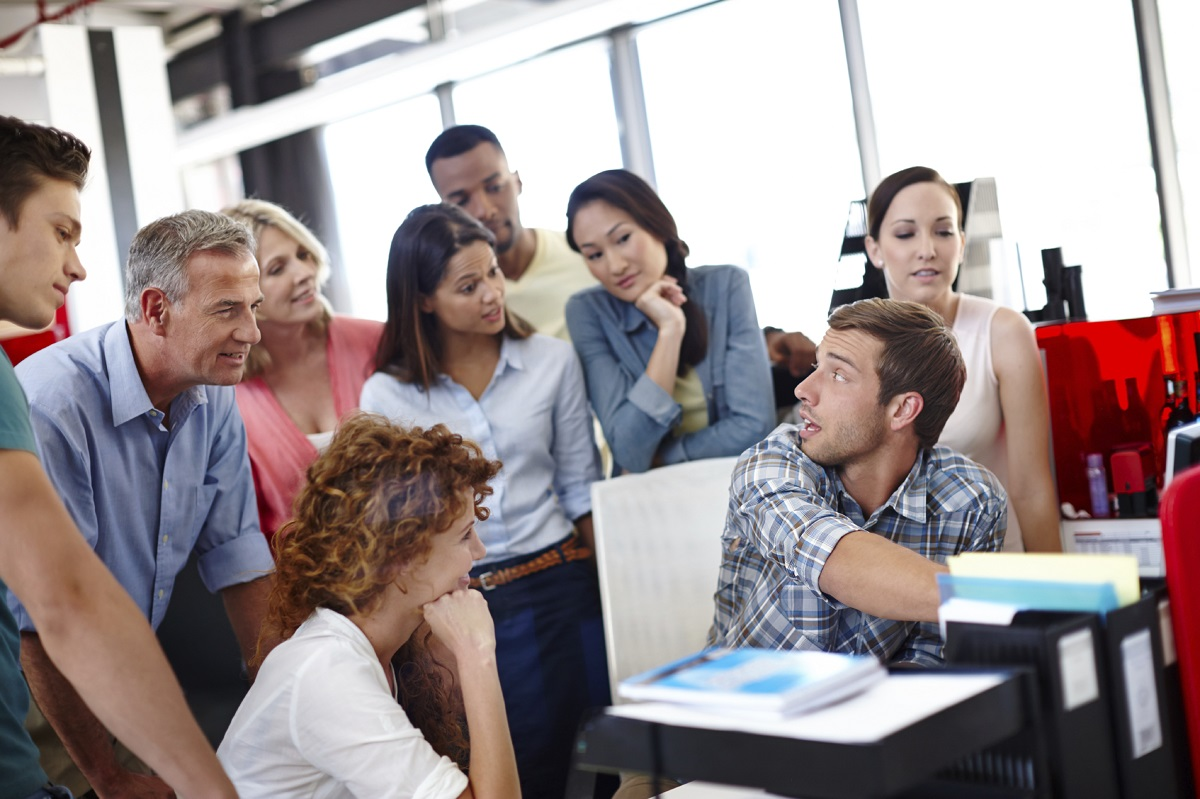 A mixed group of mature students are focused on what a particular student is doing, while he talks to the group and points to his computer screen.