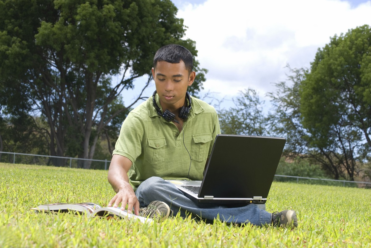 A man sitting in a park in the sun. He has is using a laptop, while consulting a book, He has headphones around his neck, ready for use.