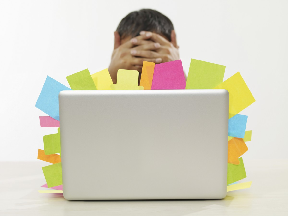 A very stressed man behind a laptop. From the edges of the laptop stick out a large number of coloured post-it notes.