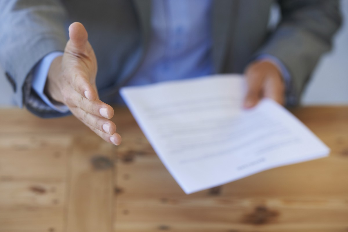 Closeup of a businessman holding a resume and offering a handshake.