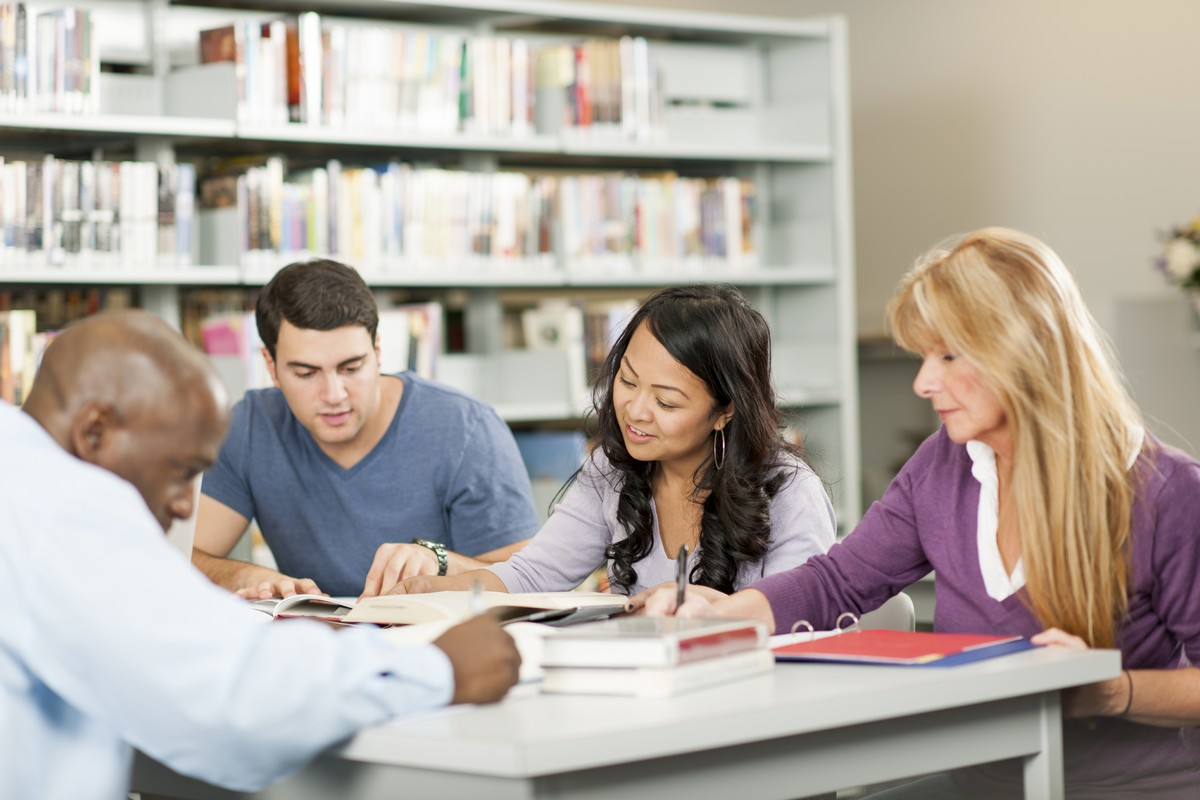 A mixed group of mature students working together in a library.