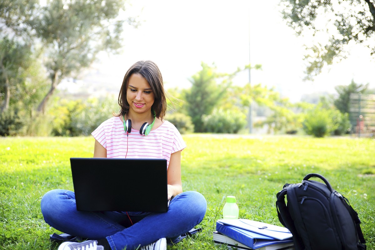 A woman using a laptop in a park to work on her studies
