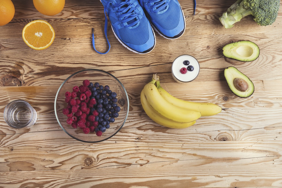 Healthy fruits and vegetables laid out on a wooden table with a glass of water and a pair of blue running shoes.