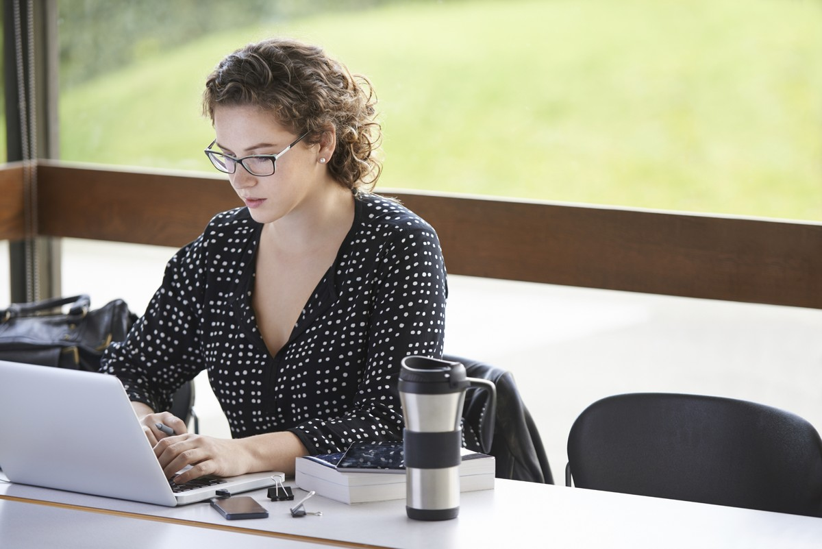 A woman is at a desk, working intently on her laptop, with a book, external hard drive, tablet and travel mug of tea by her side.