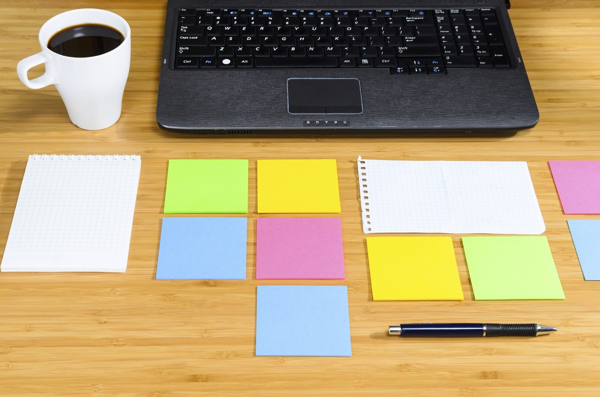 A highly organised layout of coloured post-it notes with a pen, cup of coffee and laptop on a wooden desk.