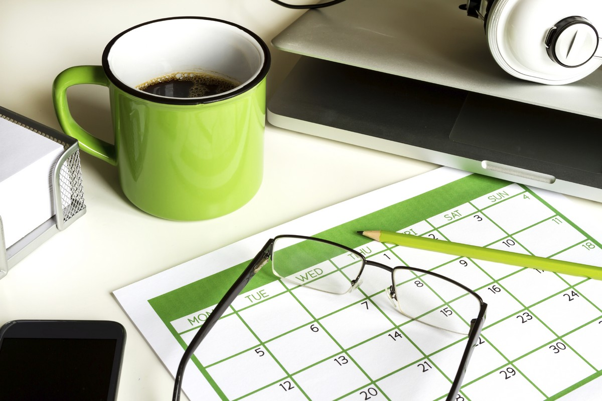 A calendar with a pencil, ready to start planning. There is a laptop, smartphone, mug of coffee and pair of eye glasses near by.