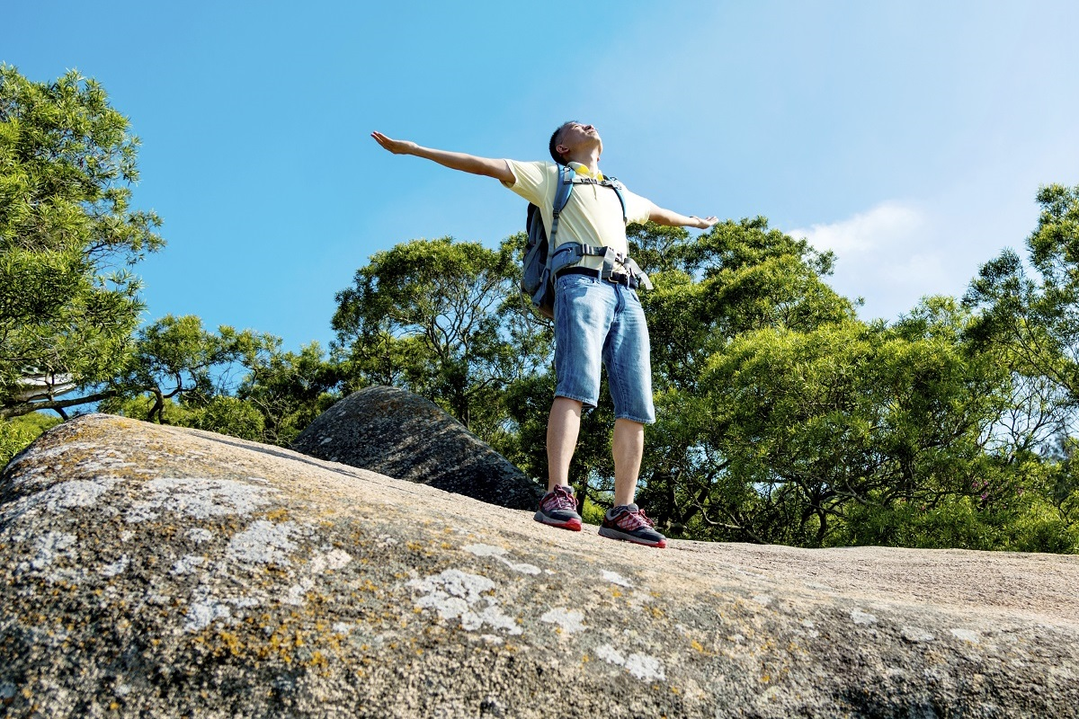 A male backpacker on top of a rock outcrop with his arms and hands raised in the air.