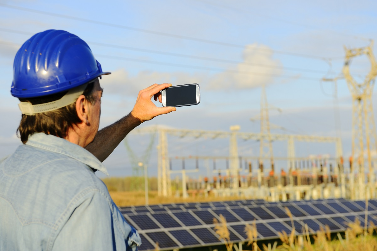 An engineering student using his smart phone to take a photo of a solar power facility.